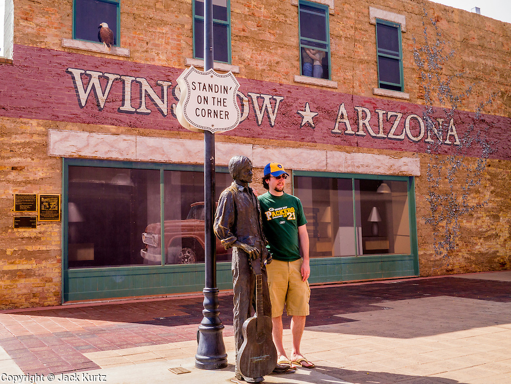 """15 JULY 2012 - WINSLOW, AZ: Tourists with the statue of Jackson Browne in the Standin' on the Corner park at the intersection of Kinsley Avenue and Second Street in Winslow, AZ. The park is based on the Eagles song, written by Jackson Browne and Glenn Frey, the second verse is """"Well, I'm a standing on a corner, In Winslow, Arizona, And such a fine sight to see. It's a girl, my lord .In a flatbed Ford, Slowin' down to take a look at me"""" The park has a statue of Jackson Browne and flatbed Ford parked nearby. There is also a mural of the scene on a wall behind the statue.       PHOTO BY JACK KURTZ"""
