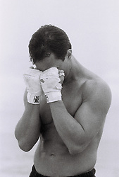 man covering face with hands covered in boxing wraps