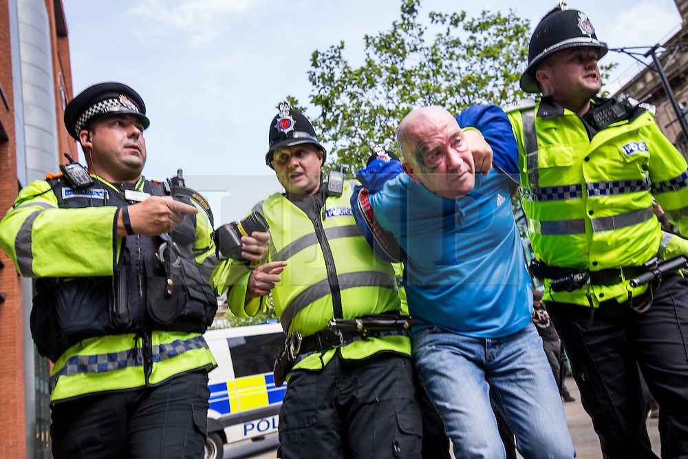"© Licensed to London News Pictures . 22/08/2015 . Manchester , UK . A far-right protester is detained . Far-right nationalist group , "" North West Infidels "" and Islamophobic , anti-Semitic and white supremacist supporters , hold a rally in Manchester City Centre . Photo credit : Joel Goodman/LNP"