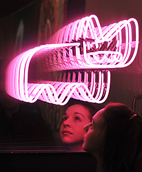 © Licensed to London News Pictures. 23/03/2012. London, UK. Bonham's employee, Victoria Livesey looks at a light piece by artist Pure Evil (b. 1968) Infinite Neon Bunny 2011 neon in two way mirror, in a perspex box 70 by 80 cm. 27 9/16 by 31 1/3 in. This work was executed in 2011. Estimate: £1,500 - 2,000,  A photocall of Bonham's Urban Art Sale including Seventeen art works by the celebrated graffiti artist, Banksy, which are to be sold at Bonhams, London, ahead of the Urban Art Sale, which takes place on 29 March 2012. . Photo credit : Stephen SImpson/LNP