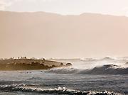 Surfers gathered on the beach at Banzai Pipeline, a surf reef break in Pupukea, O'Ahu, Hawai'i