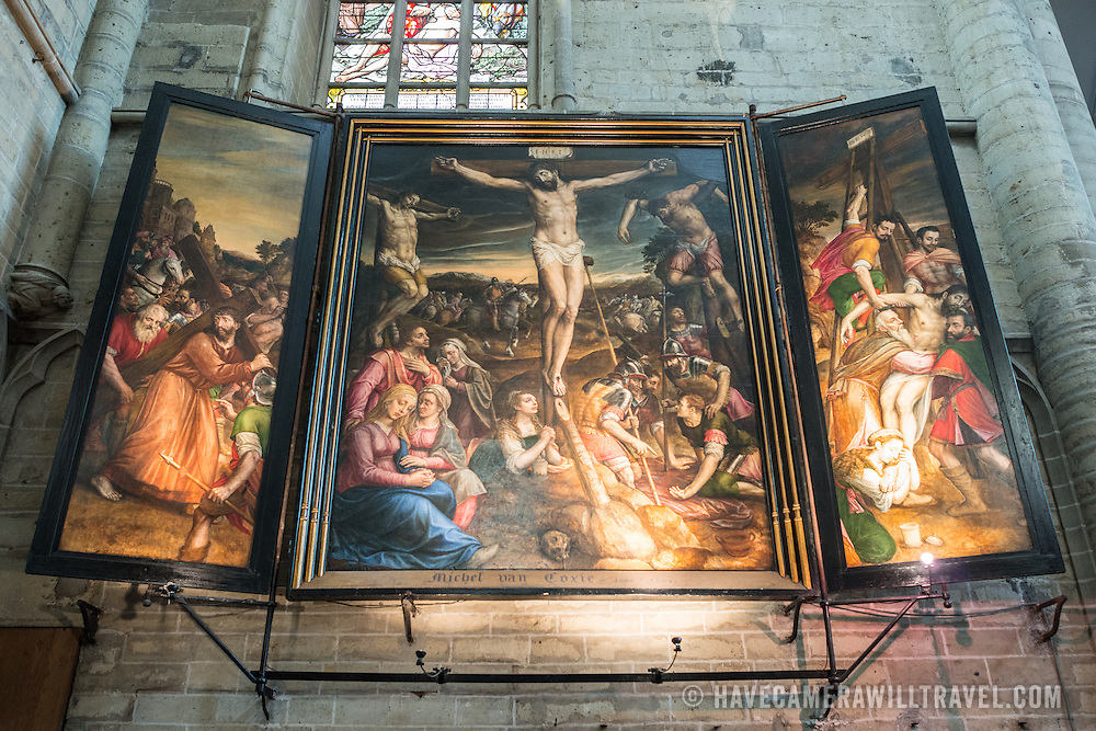 A triptych painting of the crucifixion of Christ at the Cathedral of St. Michael and St. Gudula (in French, Co-Cathédrale collégiale des Ss-Michel et Gudule). A church was founded on this site in the 11th century but the current building dates to the 13th to 15th centuries. The Roman Catholic cathedral is the venue for many state functions such as coronations, royal weddings, and state funerals. It has two patron saints, St Michael and St Gudula, both of whom are also the patron saints of Brussels.