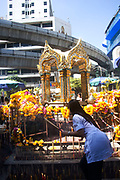 The Thao Maha Brahma Buddha sits at street level beneath the lines of the BTS skytrain, near Ratchadamri on the way to Pratunam. People come throughout the day to place flowers and incense to bless the Buddha.