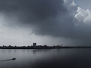 View of west lake in Hanoi with cityscape and cloudy sky in background. Vietnam, Asia. A tiny boat sail on the lake waters.