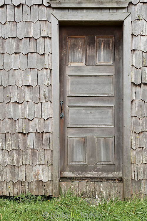 Close up of wooden shingle tiles and door, exterior of Church of Vilupulli, Chiloe Island, Chile