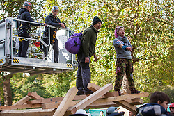 London, UK. 9 October, 2019. Police officers use a JCB cherry picker to arrest climate activists from Extinction Rebellion who had climbed on top of a wooden structure to block Birdcage Walk on the third day of International Rebellion protests.
