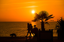 © Licensed to London News Pictures. 18/07/2018. Aberystwyth, UK. People are silhouetted as the walk along the the promenade at sunset in Aberystwyth on the west cast of Wales. The heatwave is set to continue with temperatures expected to exceed 30∫c again by the end of the week. Photo credit: Keith Morris/LNP
