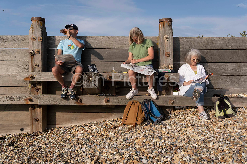 Staycationers sit above beach shingle on a wooden sea defence groyne, to enjoy the calm of a low-tide evening, on 25th July 2021, in Whitstable, Kent, England.