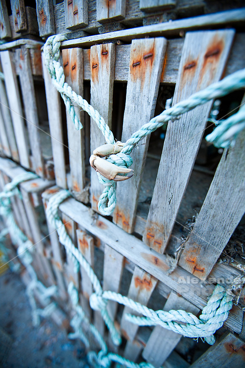 Newport, RI state fishing pier- old style wood lobster pot with a claw left by a passer by - lobstermen store huge piles of pots on the pier