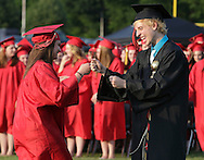 Port Jervis graduation grand marshall Eric Delarede fists bumps another senior atthe start of graduation ceremonies on Friday, June 21, 2013.