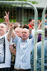 The English Defence League (EDL) return to Sheffield to lay flowers at Sheffield War Memorial which is fenced off to stop counter protesters occupying the whole of Barkers Pool. From inside the fenced off area  the EDL face the small contingent of Anti EDL protestors on the steps of Sheffield City Hall and celebrate their victory<br /> <br /> 8 June 2013<br /> Image © Paul David Drabble<br /> www.pauldaviddrabble.co.uk