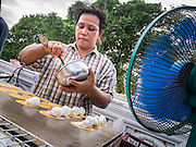 """27 NOVEMBER 2012 - BANGKOK, THAILAND:  A food vendor prepares snacks on a street in front of Wat Saket, during the temple's fair in Bangkok. Wat Saket, popularly known as the Golden Mount or """"Phu Khao Thong,"""" is one of the most popular and oldest Buddhist temples in Bangkok. It dates to the Ayutthaya period (roughly 1350-1767 AD) and was renovated extensively when the Siamese fled Ayutthaya and established their new capitol in Bangkok. The temple holds an annual fair in November, the week of the full moon. It's one of the most popular temple fairs in Bangkok. The fair draws people from across Bangkok and spills out in the streets around the temple.   PHOTO BY JACK KURTZ"""