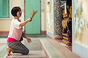 06 JUNE 2013 - BANGKOK, THAILAND:   A woman prays with incense at Wat Bhoman Khunaram. Wat Bhoman Khunaram on Sathu Pradit Road in Bangkok, is considered the most beautiful Chinese temple in Thailand. The temple was built in a blend of Thai, Chinese and Tibetan styles. It was built in the 1959 and is a Mahayana Buddhist temple (most Thais are Theravada Buddihists). There is a monastery on the temple grounds and many boys go to the temple to become monks and learn Chinese Buddhist rituals and Chinese language.      PHOTO BY JACK KURTZ