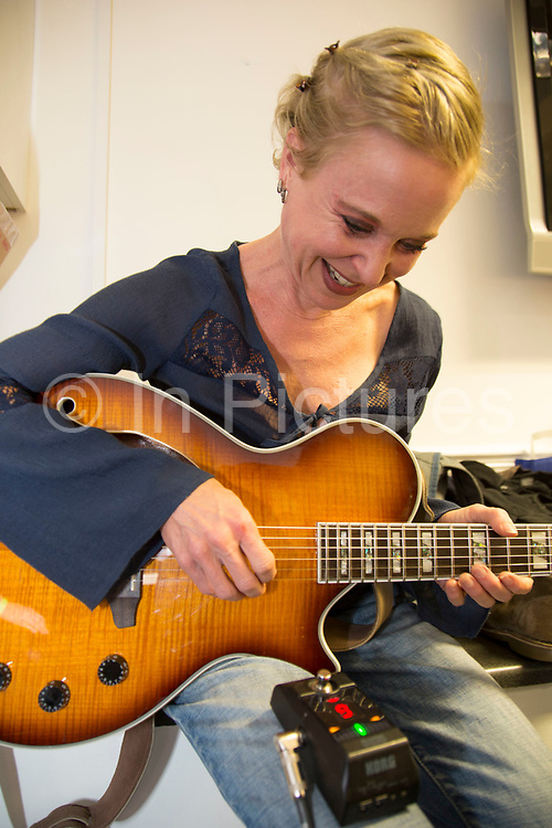 Singer and guitarist Kristin Hersh tuning up her guitar backstage. Throwing Muses at the Islington Assembly Hall, London, UK. Throwing Muses are an alternative rock band founded in 1980. The group was originally fronted by two lead singers, Kristin Hersh, and Tanya Donelly. Known for performing music with shifting tempos, creative chord progressions, unorthodox song structures, and surreal lyrics, the group was set apart from other contemporary acts by Hersh's stark, writing style, David Narcizo's unusual drumming techniques almost totally without cymbals and Bernard Georges' driving baselines.