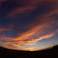 orange, yellow, blue, sky, sunset, sunrise, wide-angle photography, fish-eye lens, clouds, horizon line, bending, houses, telephone lines, poles,