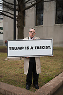 Matt Sisson, age 57, makes a statement the morning of Trump's inauguration.  Sisson said he is respectful of the day -- that's why he's wearing a suit. But he wanted to protest Trump. The sign cost $109 to have made.<br />