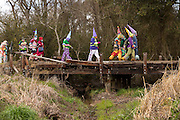 Costumed revelers walk across an old wooden bridge during the Faquetigue Courir de Mardi Gras chicken run on Fat Tuesday February 17, 2015 in Eunice, Louisiana. The traditional Cajun Mardi Gras involves costumed revelers competing to catch a live chicken as they move from house to house throughout the rural community.