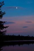 The woods of Baxter State Park are silhouetted against the twilight sky as the moon rises over the remains of sunset.