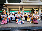 """04 SEPTEMBER 2015 - BANGKOK, THAILAND:  Classical Thai dancers perform in front of the Erawan Shrine Friday. A """"Holy Religious Ceremony for Wellness and Prosperity of our Nation and Thai People"""" was held Friday morning at Erawan Shrine. The ceremony was to regain confidence of the Thai people and foreign visitors, to preserve Thai religious customs and traditions and to promote peace and happiness inThailand. Repairs to Erawan Shrine were completed Thursday, Sept 3 after the shrine was bombed on August 17. Twenty people were killed in the bombing and more than 100 injured. The statue of the Four Faced Brahma in the shrine was damaged by shrapnel and a building at the shrine was damaged by debris.    PHOTO BY JACK KURTZ"""