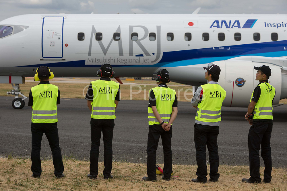 Ground crew technicians watch a Mitsubishi MRJ aircraft Mitsubishi regional Jet before its air display at the Farnborough Airshow, on 18th July 2018, in Farnborough, England.