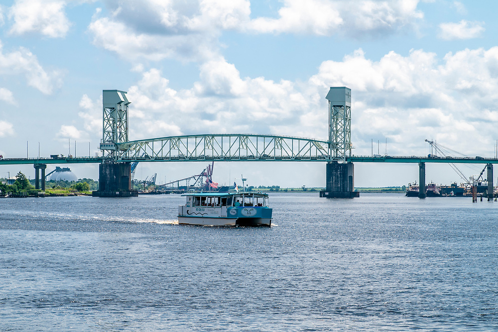 The Wilmington Water Tours pontoon boat cruises up the Cape Fear River with the Cape Fear Memorial Bridge in the background in Wilmington, North Carolina on Monday, August 9, 2021. Copyright 2021 Jason Barnette
