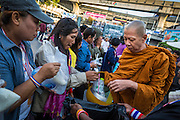 """15 JANUARY 2014 - BANGKOK, THAILAND: A Buddhist monk collects alms from protestors at the main protest site for Shutdown Bangkok. Tens of thousands of Thai anti-government protestors continued to block the streets of Bangkok Wednesday to shut down the Thai capitol. The protest, """"Shutdown Bangkok,"""" is expected to last at least a week. Shutdown Bangkok is organized by People's Democratic Reform Committee (PRDC). It's a continuation of protests that started in early November. There have been shootings almost every night at different protests sites around Bangkok. The malls in Bangkok are still open but many other businesses are closed and mass transit is swamped with both protestors and people who had to use mass transit because the roads were blocked.    PHOTO BY JACK KURTZ"""