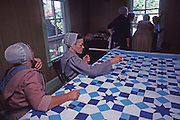 "Conservative ""Horse and Buggy"" Mennonite women quilt while men erect a barn outside."