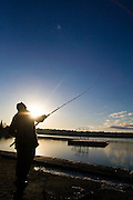 A fisherman casts his fishing rod into Green Lake, stocked with thousands of rainbow trout each year by the Department of Fish and Wildlife, in Seattle, Washington.