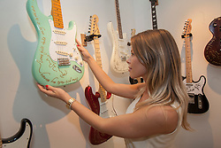 © licensed to London News Pictures. London, UK 13/08/2012. An admirer looking at the guitars which have been used by Ronnie Wood shown at the 'A Major Retrospective Of 50 Years Of Rock And Roll' exhibition in central London.  Photo credit: Tolga Akmen/LNP