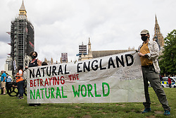 Stop HS2 activists hold a banner criticising Natural England at a Kill The Bill protest in Parliament Square against the Police, Crime, Sentencing and Courts (PCSC) Bill 2021 as MPs consider amendments to the Bill in the House of Commons on 5th July 2021 in London, United Kingdom. The PCSC Bill would grant the police a range of new discretionary powers to shut down protests, including the ability to impose conditions on any protest deemed to be disruptive to the local community, wider stop and search powers and sentences of up to 10 years in prison for damaging memorials.