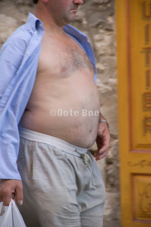 overweight middle aged man walking with his shirt open