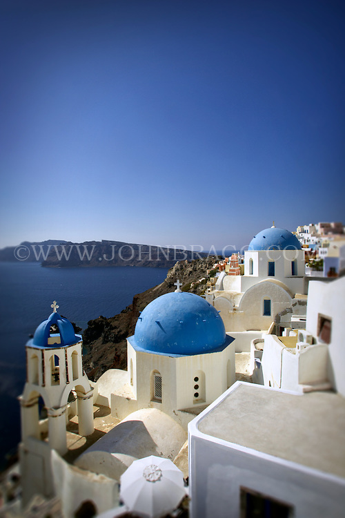 Buildings on a cliff, blue domed rooftops, view of the Aegean sea, Santorini, Greece.