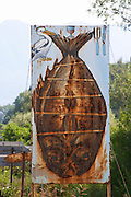 Rusty road side sign with a drawing of a fish, a pelican and glass, knife and fork, pointing the way to a nearby restaurant. Near Dupilo, Golubovic Montenegro, Balkan, Europe.