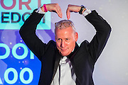 Jim White, sky sports demonstrates the Mobot for the game of heads and tails - UK charity, Sport for Freedom (SFF), marks Anti-Slavery Day 2015 by hosting a charity Gala Dinner, supported by Aston Martin, on Thursday 15th October at Stamford Bridge, home of Chelsea Football Club. This inaugural event brought together people from the world of sport, entertainment, media, and business to unite behind a promise to tackle the issue of modern day human trafficking and slavery.  <br /> Hosted by Sky presenters Sarah-Jane Mee and Jim White, the Sport for Freedom Gala Dinner includes guests such as jockey AP McCoy OBE; Denise Lewis, former British Olympic Gold Medal winner; BBC Strictly star, Brendan Cole; Al Bangura, former Watford FC player and Sport for Freedom Ambassador who was trafficked from Africa to the UK at the age of just 14yrs old; Made in Chelsea star, Ollie Proudlock; ITV weather presenter, Lucy Verasamy; Sky Sports F1 presenter and SFF Ambassador, Natalie Pinkham; Premier League footballers Ryan Bertrand of Southampton FC and Troy Deeney of Watford FC and champion boxer, Anthony Joshua; and The UK's first independent Anti Slavery Commissioner, Kevin Hyland OBE, who highlighted the issues of modern day slavery that face the UK and world today. <br /> The evening concluded with chart topping music from 'Naughty Boy'. <br /> Sport for Freedom are also joining forces with the Premier League Academies for an international  'Football for Freedom' tournament with their U16's players that will also involve educating those taking part about the issues surrounding modern day slavery. The final will take place at Liverpool FC's Academy on Anti-Slavery Day, 18th October.