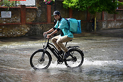 © Licensed to London News Pictures. 24/06/2021. London, UK. A cyclists rides through a river of water in St John's Wood, North London, where a burst pipe has has cause flooding across a number of streets in the area. Photo credit: Ben Cawthra/LNP