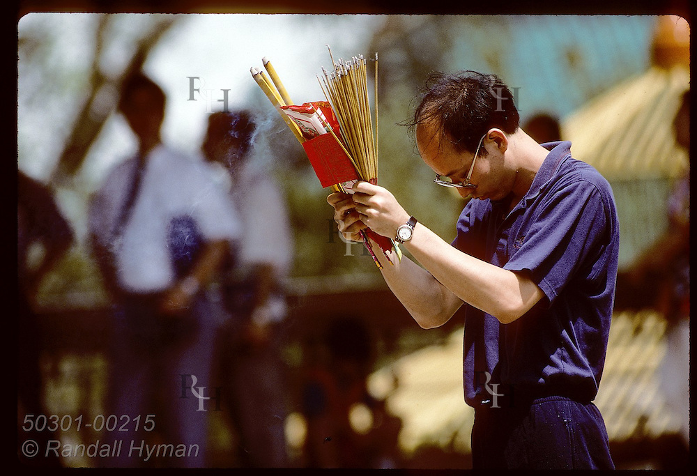 Man prays for good fortune with burning joss sticks at Wong Tai Sin, a Chinese temple in Kowloon Hong Kong