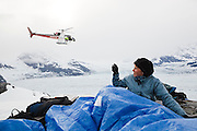 Julie Markus, graduate student at Ohio State University, takes pictures as Shad O'Neel, USGS glaciologist, flies off in a helicopter above camp at Columbia Glacier, near Valdez, Alaska.