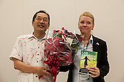 """Ex SDP politian, Ryoichi Hattori (left) presents flowers to rape Survivor and activist, Catherine """"Jane"""" Fisher at a press conference to publicise her book  in the First Office Building of the Members of the House of Representatives, Nagatacho, Tokyo, Japan, Friday July 18th 2014. Ms Fisher was raped near Yokusuka US Naval Base in Kanagawa in 2002 and has been campaign for the rights of rape victims in Japan since after finding the US Military and Japanese police obstructive and uninterested in bringing her attacker to justice."""