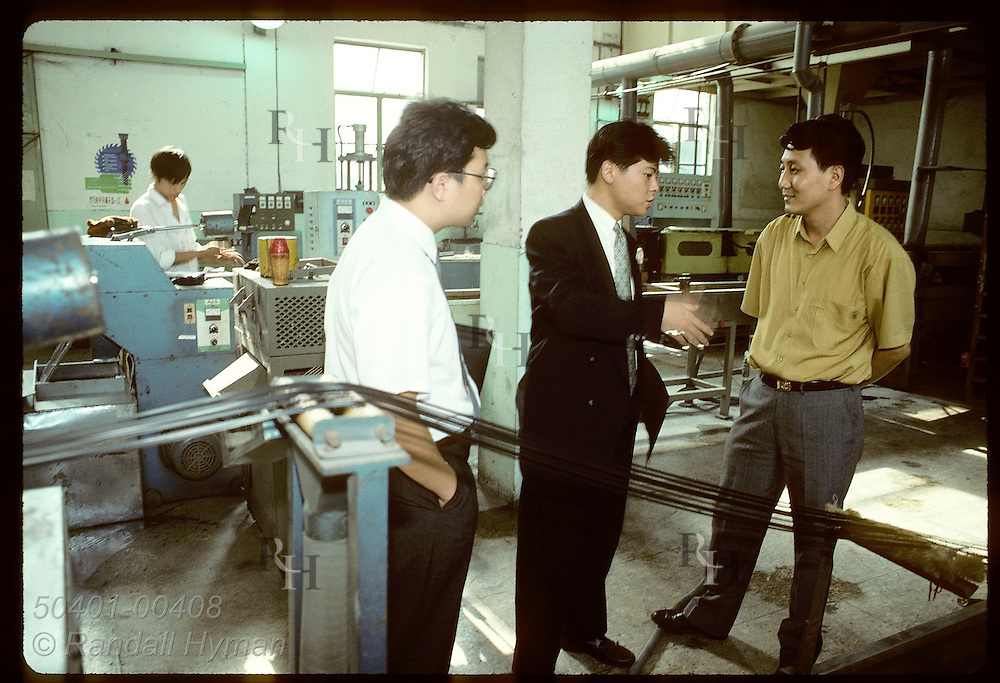 Monsanto rep Sam Chi talks to manager inside plant that recycles ABS plastic in Shanghai. China