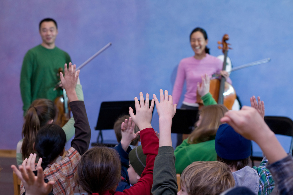 Children a the Meadowbrook school raise their hands to question violist Burchard Tang and cellist Priscilla Lee. Tang and Lee were participants in the Kingston Rhode Island Chamber Music Festival in 2008.