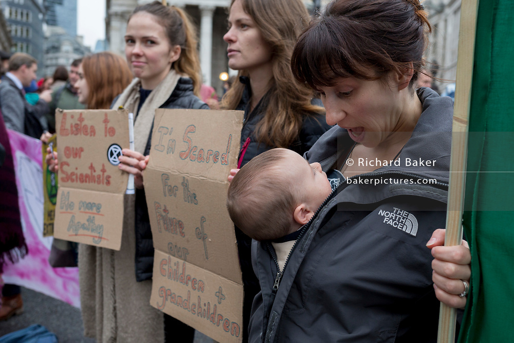 A mother and child environmental activists protest about Climate Change during the blockade at the junction at Bank in the heart of the capital's financial district, the City of London aka the Square Mile, on the seventh day of a two-week prolonged worldwide protest by members of Extinction Rebellion, on 14th October 2019, in London, England.