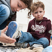 10 year old Maha helps her 3 year old brother Hamad to dress in they rent in Kara Tepe camp, Lesvos, Greece