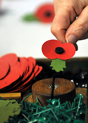 © Licensed to London News Pictures. 07/11/2011. Richmond, UK. A man assembles a poppy on a platform designed to enable a person with the use of one hand to use it. Red Poppies being made in The Poppy Factory in preparation for sale in 2012, Richmond, Surrey today 7th November.  The factory has been supplying the poppy, crosses and wreathes to the British Legion for almost 90 years. It is staffed by veterans, many whom of which are injured, sick or wounded of all ages. Photo credit : Stephen Simpson/LNP