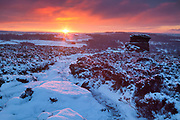 Fiery yet fleeting dawn light highlights the path from Over Owler Tor to Mother Cap in the Peak District. A snowy winter landscape in England, UK.