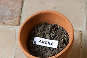 Plant pot with soil sample to illustrate different soil types, part of a series: clay, argile. Chateau Villerambert-Julien near Caunes-Minervois. Minervois. Languedoc. Terroir soil. France. Europe. Clay.