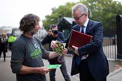© Licensed to London News Pictures. 09/10/2019. London, UK. Chancellor of the Duchy of Lancaster Michael Gove talks to an Extinction Rebellion protester at the back of Downing Street. Police continue to attempt to clear roads on the third day of the protest . Photo credit: George Cracknell Wright/LNP