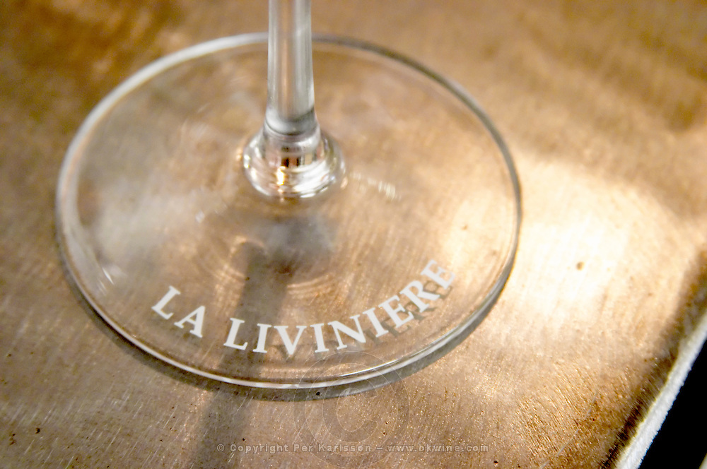 The stem and foot of a glass with the text La Liviniere, Minervois, Languedoc, France