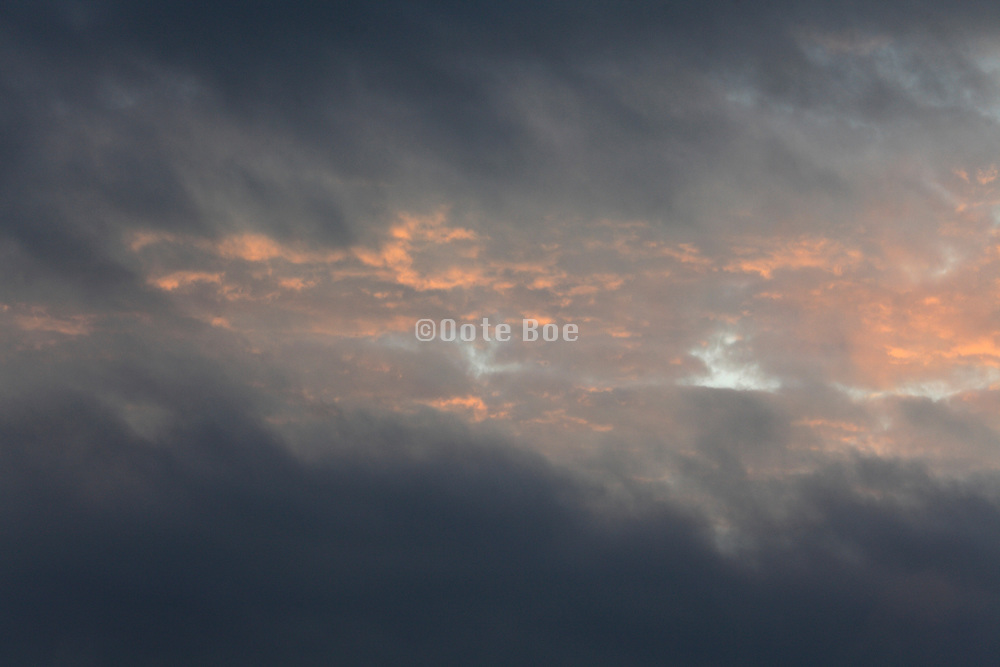 wind swept cloud formations with orange sunlight