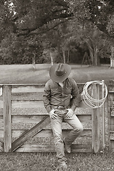 cowboy leaning against a wooden fence