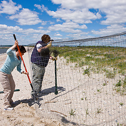 Orla Molloy (left) and Laura Saucier of the Connecticut Department of Environmental Protection build an exclosure around the nest of an endangered piping plover on Long Beach in Stratford, Connecticut. Adjacent to the Great Meadows Unit of McKinney National Wildlife Refuge.